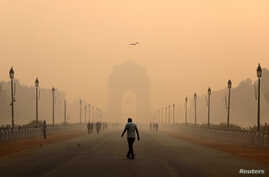 A man walks in front of the India Gate shrouded in smog in New Delhi, India, Oct. 29, 2018.