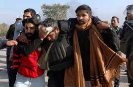 Pakistani police officers help their injured colleague during a clash with protesters in Islamabad, Pakistan, Nov. 25, 2017. Police launched an operation to clear an intersection where an Islamist group's supporters had camped out for the last 20 day