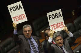"Deputies from opposition parties carry signs that read in Portuguese ""Temer Out,"" during a key vote by the lower chamber of Brazil's Congress on whether to suspend Brazil's President Michel Temer and put him on trial over an alleged bribery scheme, i"