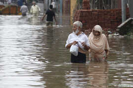 A couple wades through a flooded street after heavy rains in Lahore, Pakistan, Sept. 4, 2014.