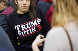 "FILE - A woman wears a shirt reading ""Trump Putin '16"" while waiting for Republican presidential candidate Donald Trump to speak at a campaign event at Plymouth State University in Plymouth, N.H., Feb. 7, 2016. In a recent outreach to Putin, Trump n"