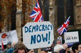 FILE - Pro-Brexit demonstrators wave flags and banners outside Parliament in London.
