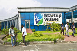 FILE - Employees stand outside the Start-up Village in Kinfra High Tech Park in the southern Indian city of Kochi.