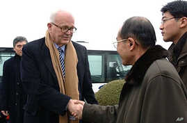 Stephen Bosworth (C), US special envoy to North Korea, shakes hands with an unidentified North Korean official upon his arrival at Pyongyang airport, 08 Dec 2009