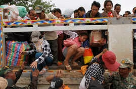 Cambodian migrant workers get off a Thai truck upon their arrival from Thailand at a Cambodia-Thailand's international border gate in Poipet, Cambodia, June 17, 2014.