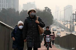 A woman and a child wearing masks walk hands in hands as a cyclist covers his nose for protection against the pollution on a pedestrian overhead bridge on a polluted day in Beijing, Sunday, Dec. 20, 2015.