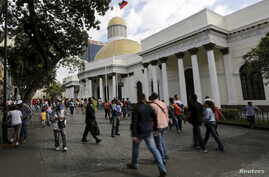 People walk past the National Assembly building in Caracas, Venezuela, Dec. 22, 2015.
