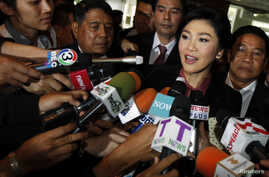 Ousted former Prime Minister Yingluck Shinawatra talks to reporters as she arrives at Parliament before the National Legislative Assembly meeting in Bangkok, Jan. 9, 2015.