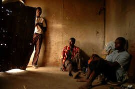 FILE - Illegal Zimbabwean immigrants who work as farm laborers are seen inside their room on a farm near the Beitbridge border post, between South Africa and Zimbabwe, in the Limpopo Province, in March 2006.