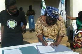 Traditional Authority Chitera signs by-laws as GENET's Joyce Mkandawire looks on (GENET)