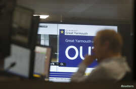A traders works as EU Referendum results come in on a giant screen behind, in London, Britain, June 24, 2016.