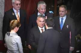 Hungarian Prime Minister Viktor Orban (C) congratulates re-elected Hungarian President Janos Ader (Front) in the presence of Ader's wife, Anita Herczegh (L), Deputy PM in charge of national politics Zsolt Semjen (Back C), and Fidesz faction leader La