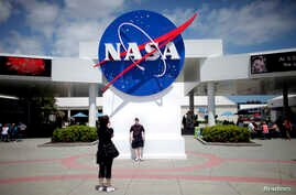 FILE - Tourists take pictures of a NASA sign at the Kennedy Space Center visitors complex in Cape Canaveral, Florida.