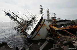 A partially capsized fishing ship is seen after Typhoon Meranti made landfall, in Kaohsiung, Taiwan, September 15, 2016.