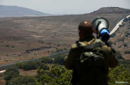 An Israeli soldier speaks over a megaphone to people which stand next to the border fence between Israel and Syria from its Syrian side as it is seen from the Israeli-occupied Golan Heights near the Israeli Syrian border July 17, 2018.