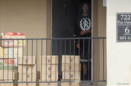 A man emerges from the apartment unit to get boxes of food delivered by the Red Cross and the North Texas Food Bank in The Ivy Apartments complex where a man diagnosed with the Ebola virus was staying in Dallas, Texas, October 2, 2014.