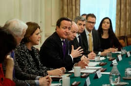 Britain's Prime Minister David Cameron (C) sits with Secretary of State for Culture Media and Sport, Maria Miller (3rd L) as he hosts an Internet safety summit at Number 10 Downing Street in London, Nov.18, 2013.