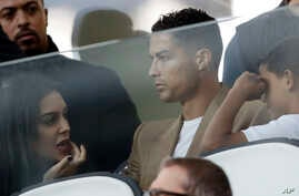 FILE - Soccer superstar Cristiano Ronaldo, center, flanked by his girlfriend Georgina, left, and his son Cristiano Jr, sits in the stands during a Champions League game, at Allianz stadium in Turin, Italy, Oct. 2, 2018.