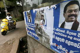 A woman rides her bike past the election posters of Sri Lanka's former Sri Lankan President Mahinda Rajapaksa for upcoming general election in Colombo, July 14, 2015.