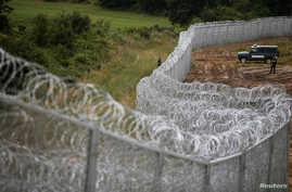 Bulgarian border police stand near a barbed wire fence on the Bulgarian-Turkish border, July 17, 2014.
