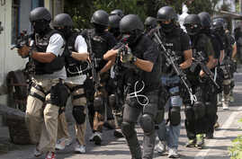 Members of Indonesian police anti-terror unit Special Detachment 88 move into positions as they prepare for a raid in Solo, Central Java, Indonesia, September 26, 2012.