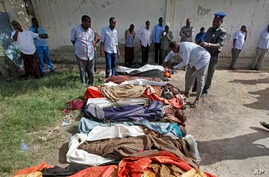 Somalis observe bodies which were brought to and displayed in the capital Mogadishu, Somalia, Aug. 25, 2017.