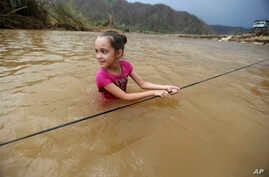 Ruby Rodriguez, 8, looks back at her mother as she wades across the San Lorenzo Morovis river with her family, since the bridge was swept away by Hurricane Maria, in Morovis, Puerto Rico, Sept. 27, 2017. They were returning to their home after visiti