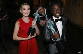 """Millie Bobby Brown, left, and Caleb McLaughlin appear backstage with the awards for outstanding performance by an ensemble in a drama series for """"Stranger Things"""" at the 23rd annual Screen Actors Guild Awards at the Shrine Auditorium & Expo Hall, Jan"""