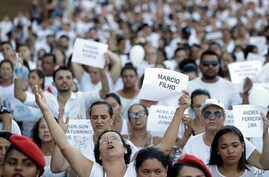 Friends and relatives hold signs with the names of victims, during a march paying homage to the victims of a mining dam collapse a week ago, in Brumadinho, Brazil, Friday, Feb. 1, 2019.