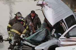 First responders work to free a passenger from a truck involved in an accident on Interstate 35 during severe weather in Moore, Okla., May 6, 2015.