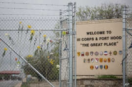 Flowers decorate a fence outside of Fort Hood's east gate, April 6, 2014, in Killeen, Texas, in honor of those killed and wounded in the Fort Hood shooting on April 2.