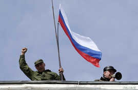 FILE - A man holds a Russian flag on the roof of the a navy building in Sevastopol, March 19, 2014.