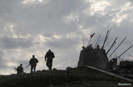 Pro-Russian separatists walk at a destroyed war memorial on Savur-Mohyla, a hill east of the city of Donetsk, August 28, 2014.