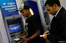 Men withdraw cash from automated teller machines at a Mercantil bank branch in Caracas, Venezuela, Aug. 20, 2018.