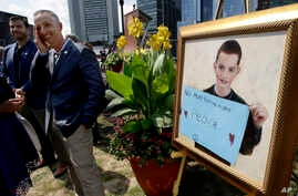 Bill Richard, second from left, father of Boston Marathon bombing victim Martin Richard, stands next to a painting of Martin, right, at the conclusion of groundbreaking ceremonies for a park named after his late son, Aug. 16, 2017, in Boston. Martin