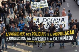 "Civil police demand better labor conditions as they carry a banner that reads in Portuguese ""The priority of the police is the people, the priority of the government is the Olympics"" in Rio de Janeiro, Brazil, June 27, 2016."