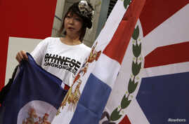 FILE - A protester, carrying a former Hong Kong colonial flag, rallies against China's control over the internal affairs of the former British colony, outside the British Consulate in Hong Kong June 15, 2014.
