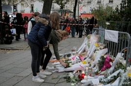 People lay flowers as part of a memorial to victims a day after more than 120 people were killed in a series of attacks in Paris, Nov. 14, 2015.