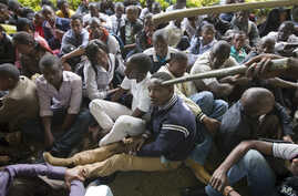 A Kenyan student is prodded in the head by a riot policeman's club as he and others are forced to sit in a group after surrendering to riot police in order to escape from a tear-gas-filled building inside Nairobi University's main campus in downtown