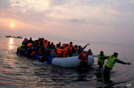FILE - volunteers help migrants and refugees on a dingy as they arrive at the shore of the northeastern Greek island of Lesbos, after crossing the Aegean sea from Turkey.