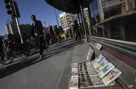 FILE - Iranian banknotes are displayed by a vendor at the side walk of the Ferdowsi Street in Tehran, Jan. 23, 2013.