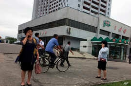Residents go about their business near one of the city's biggest department stores and shopping areas in Pyongyang, North Korea, June 10, 2018.