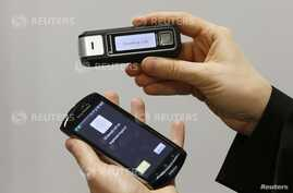 An employee of German IT-security and encryption specialist Rohde und Schwarz SIT GmbH presents a TopSec phone encryption system next to a mobile phone in Berlin, October 29, 2013.