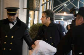 Michael Cohen arrives at his home in New York with his left arm in a sling supported by a pillow, Jan. 18, 2019.