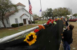 Rachel Vasquez places flowers in a fence for the victims of the shooting outside of the Sutherland Springs Baptist Church following a service held at a temporary site, Nov. 12, 2017, in Sutherland Springs, Texas.