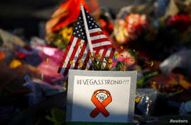 A sign and U.S. flag are pictured at a makeshift memorial in the middle of Las Vegas Boulevard following the mass shooting in Las Vegas, Nevada, Oct. 6, 2017.