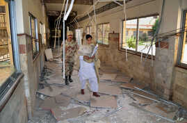FILE - A Pakistani paramilitary soldier and a nurse walk through a corridor at the Bolan Medical complex damaged by an attack claimed by the Sunni militant group Lashkar-e-Jhangvi, in Quetta, Pakistan, June 16, 2013.