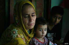 Indian Kashmiri refugee woman Nasima Bibi (L) as she sits with her granddaughter and grandson at Manak Payyan refugee camp on the outskirts of Muzaffarabad, the capital of Pakistan controlled Kashmir, Aug. 7, 2013.
