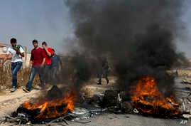 Palestinian protesters burn tires and clash with Israeli army soldiers after troops searched and measured the family house of Omar al-Abed, 20, identified by the Israeli army as the assailant in an attack at the Israeli settlement of Halamish, in pre
