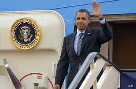 President Barack Obama waves as he gets off Air Force One upon his arrival at King Khalid International airport in Riyadh, Saudi Arabia, March 28, 2014.